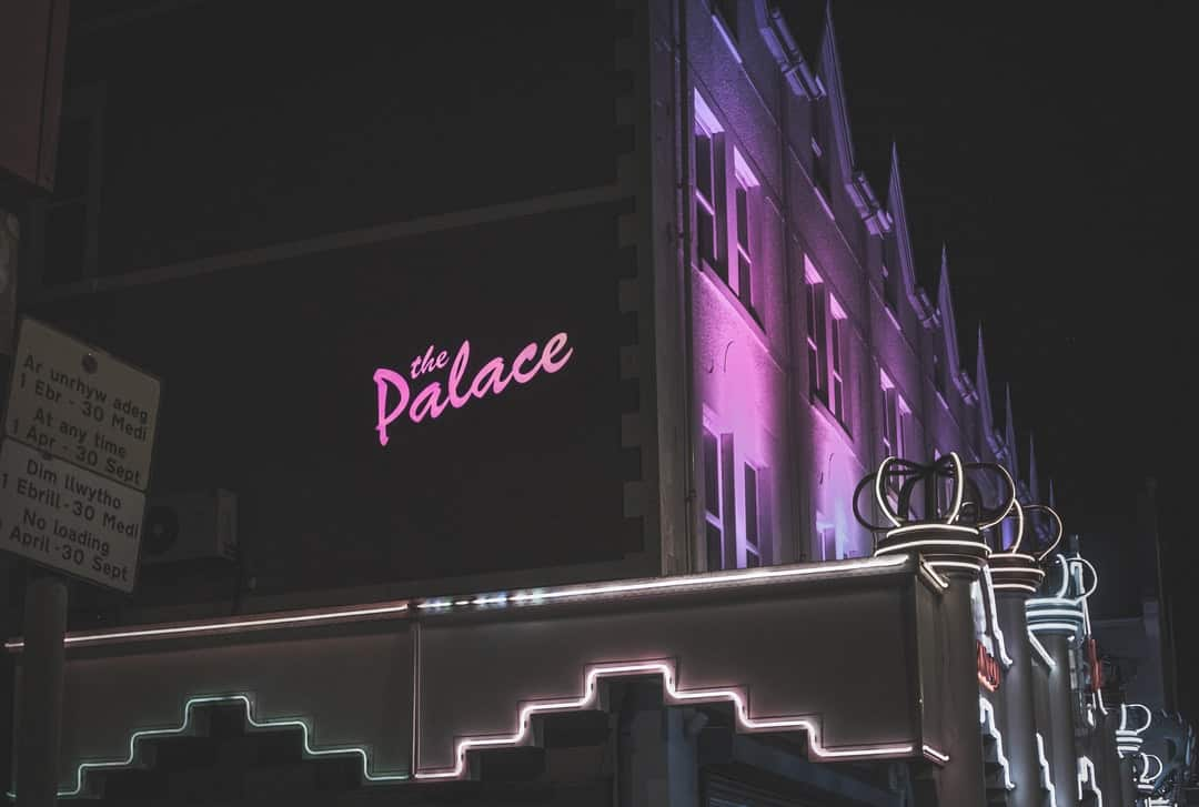 A sign on the side of a building lit up at night